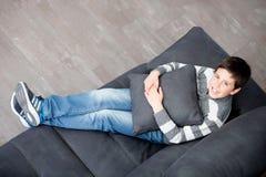 Preadolescente sonriente en el sofá en casa Fotos de archivo