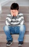 Preadolescente triste que se sienta en las escaleras en casa Imagen de archivo libre de regalías