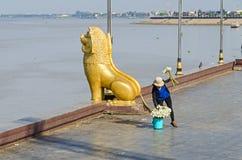 Preah Sisowath Quay dans Phnom Penh avec la statue du lion de gardien et une femme vendant des fleurs de lotus Images libres de droits