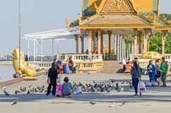 Preah Sisowath Quay et Royal Palace se garent avec beaucoup de pigeons Photos libres de droits