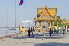 Preah Sisowath Quay et Royal Palace se garent avec beaucoup de pigeons et de personnes les alimentant Photographie stock libre de droits