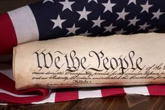 Preamble to the United States Constitution. Document text `We the People` of the preamble to the United States constitution with american flag in background Royalty Free Stock Images