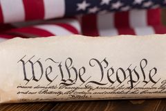 Preamble to the United States Constitution. Document text `We the People` of the preamble to the United States constitution with american flag in background Stock Photos
