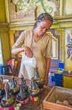 Preapre fresh Ethiopian coffee. KIEV, UKRAINE - JUNE 4, 2017: Ethiopian Tigrayan woman prepare coffee for traditional ceremony - , she pours water to jebena Stock Photography