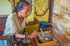 Preapring of green coffee beans. KIEV, UKRAINE - JUNE 4, 2017: The Tigrayan girl at work - she stirs up the roasting coffee beans for the ethnic Ethiopian coffee Royalty Free Stock Photos
