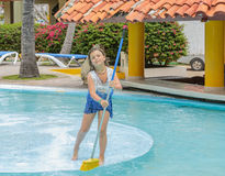 Pretty girl cleaning the swimming pool island with. Little girl standing in swimming pool island and brushing-cleaning the concrete surface with broom in Stock Photos