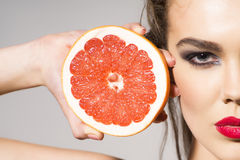 Preatty girl holding grapefruit cut in half next to the head Stock Image