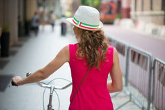 Preaty girl in hat and pink dress riding a bicycle Royalty Free Stock Photography