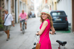 Preaty girl in hat and pink dress riding a bicycle Royalty Free Stock Images