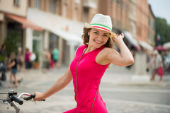 Preaty girl in hat and pink dress riding a bicycle Stock Photos