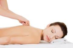 Preaty kvinna som kopplar av att masseras i brunnsortsalong. Arkivfoto