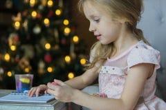 Preaty liten flickateckning nära julgranen med bokeh royaltyfri fotografi