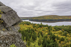 Precambrian Rock with Fall Colors and a Lake in the Background -. Outcrop of Precambrian rock in autumn with a forested lake in the distance - Algonquin royalty free stock photos