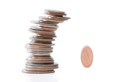 Precarious stack of coins falling Stock Photos