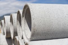 Precast concrete manholes are stored on the ground ready for con Stock Images