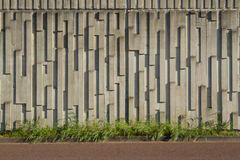Precast wall. A precast concrete wall patterned with vertical oblong textures with green grass on a horizontal plane and a red tarmac path below Royalty Free Stock Photos