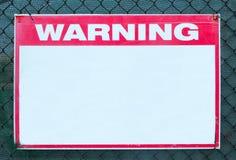 Precaución de la seguridad de la señal de peligro con el mensaje blanco en blanco en el límite de la rejilla del emplazamiento de Foto de archivo libre de regalías