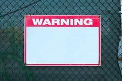 Precaución de la seguridad de la señal de peligro con el mensaje blanco en blanco en el límite de la rejilla del emplazamiento de Imagenes de archivo