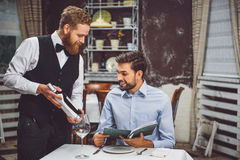 Precautionary waiter offering wine to visitor. Benevolent flunkey is staying near client, suggesting sort of nectar. Smiling customer listening attentively Royalty Free Stock Photo