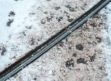 Precio de la tranvía en invierno en la ciudad Las huellas de los peatones que cruzan el metal cercan el fondo con barandilla foto de archivo libre de regalías