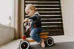 Precious Adorable Cute Little Blonde Baby Toddler Boy Kid Playing Outside on Wooden Toy Bicycle Scooter Mobile Smiling at the Came stock photos