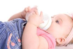 Precious baby drinking a bottle Stock Image