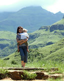 Precious baggage. A young woman carries her little blond son while walking on a mountain trail in Central Drakensberg in South Africa Stock Photography