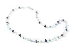 Precious beads necklace. Handmade precious gemstones (aquamarine, iolite, apatite) bead necklace  on white, shallow dof Royalty Free Stock Photography