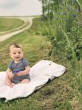 Baby boy sitting on blanket in country holding flower and grinning. Cute baby sitting on white quilt Stock Image
