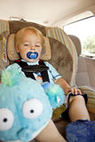 Precious Cargo. A one year old, blonde haired baby boy in a blue shirt, sitting in a car seat in the back seat of a vehicle with a blue pacifier in his mouth Stock Photography