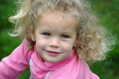 Precious child. A beautiful caucasian white girl head portrait with happy smiling expression in her pretty face, blue eyes and long light blond curly hair Royalty Free Stock Image