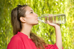 Precious cool water. Precious cool water, gorgeous young brunette with bottled water Stock Photos