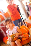 Precious Girl Riding Wagon with Her Pumpkin and Sister Stock Photo