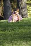 Precious ittle girl in pink dress on grass. Pretty, 3-1/2 year old girl wearing a pastel pink fancy dress, stooping down onto a lawn.  Girl has brown hair pulled Stock Image