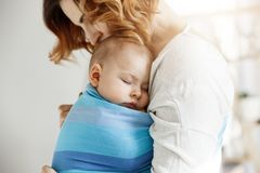 Precious little newborn boy having deep sleep at day on mother chest in blue baby sling. Mom kissing baby head and Stock Image
