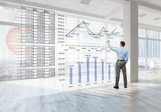 Precious metals market. Back view of elegant businessman against modern ofiice window Stock Images