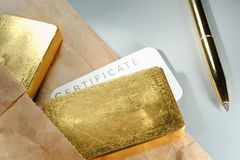 Precious metals trading. Processing and global trading of precious metals. Gold bars, certificate, pen and paper pack. Closeup Stock Photography
