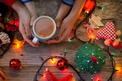 Mother and child holding together a cup of hot tea in a festive Christmas décor, waiting for San. Precious moments of holiday with mother and child royalty free stock images