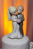 Precious Moments Wedding Cake Topper. Bride and groom precious moments wedding cake topper on top of white cake. Close up royalty free stock image
