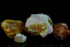 Precious opal. On a mirror and a black background Royalty Free Stock Images
