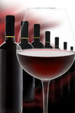 Precious Red Wine. Wineglass and bottles of precious red wine in a row Royalty Free Stock Photos