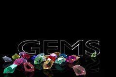 Precious stones on a black background with the words and empty space. Stock Images