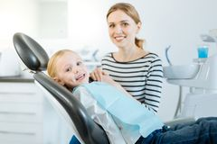 Cute little patient and her mother posing in dentist office. Precious support. Charming little girl and her mother posing for the camera while the girl sitting royalty free stock image