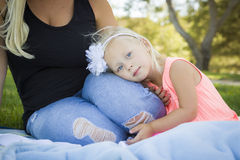 Precious Young Girl Resting on Her Mommy's Lap At Park. Beautiful Young Blue Eyed Girl Resting on Her Mommy's Lap Outside At the Park Stock Photo
