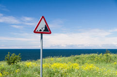 Precipice edge warning sign. Danger sea cliff hidden by grass Royalty Free Stock Photo