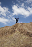Precipice of success. Businessman standing on hilltop Stock Images