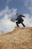 Precipice of success. Businessman climbing a mountain; metaphor for the climb to success Royalty Free Stock Photo