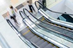 Precipitação dos povos no movimento da escada rolante borrado Fotos de Stock