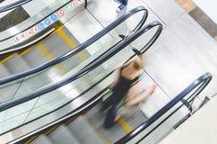Precipitação dos povos no movimento da escada rolante borrado Foto de Stock Royalty Free