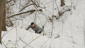 Precipitações de um atleta em uma inclinação nevado na floresta vídeos de arquivo